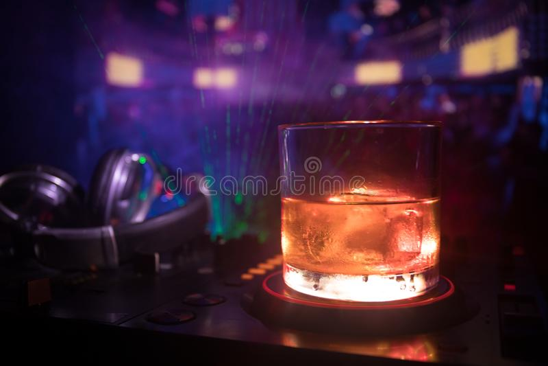 Exponeringsglas med whisky med iskuben inom på dj-kontrollant på nattklubben Dj-konsol med klubbadrinken på musikpartiet i nattkl royaltyfria bilder