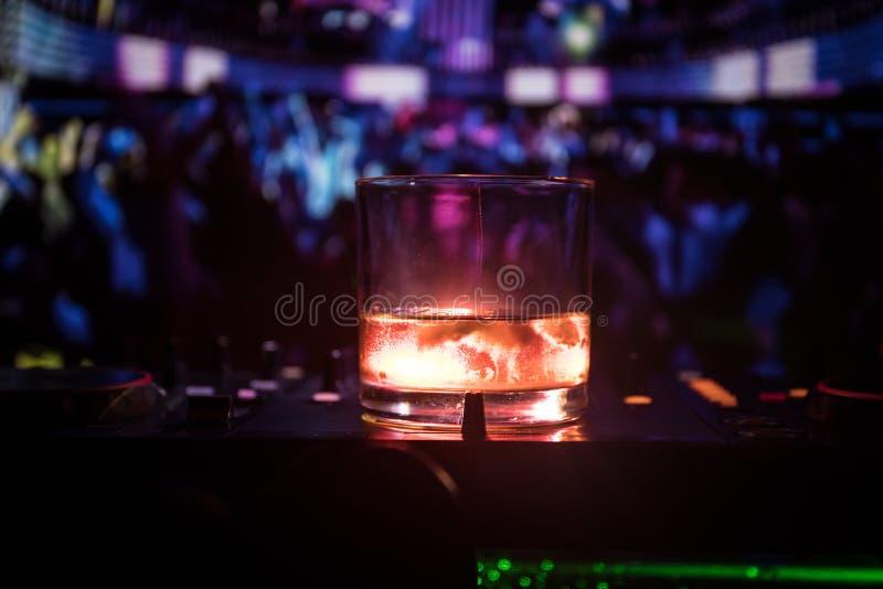 Exponeringsglas med whisky med iskuben inom på dj-kontrollant på nattklubben Dj-konsol med klubbadrinken på musikpartiet i nattkl arkivfoto