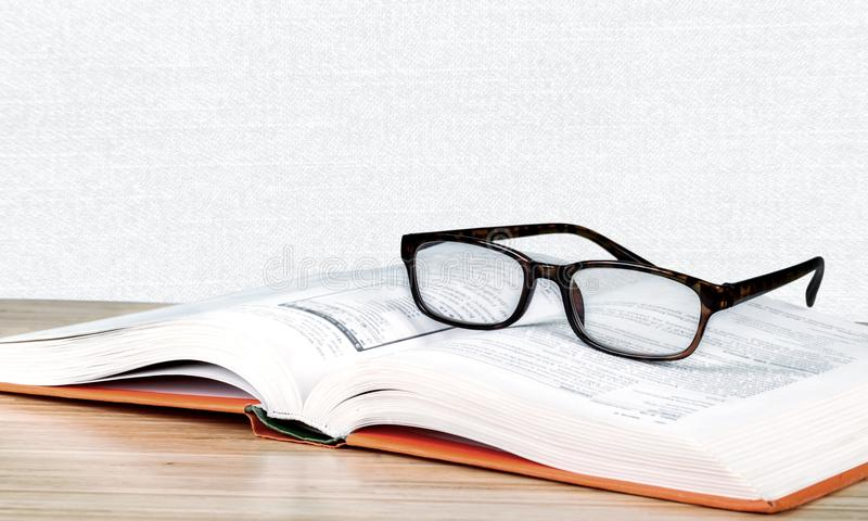 Exponeringsglas och bok för närbild svarta läs- på suddigt royaltyfria bilder