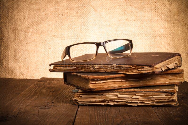 Exponeringsglas och bunt av gamla böcker på den gamla trätabellen tonat fotografering för bildbyråer