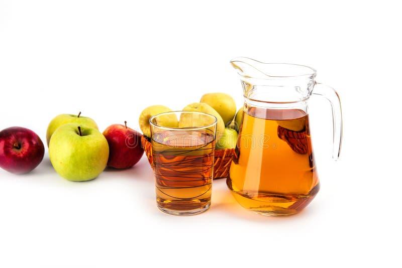 Exponeringsglas och en tillbringare av äppelmust, på vit bakgrund royaltyfri bild