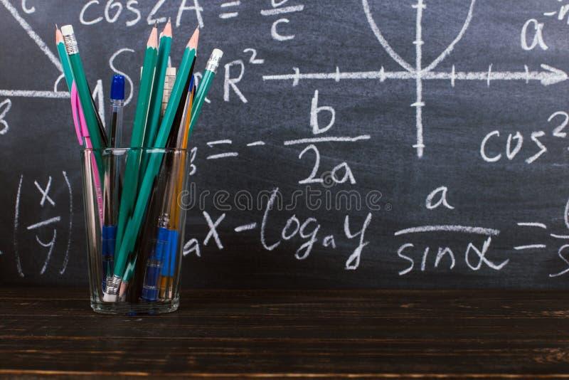 Exponeringsglas och ett exponeringsglas med blyertspennor på svart tavlabakgrund med formler Teacher' s-dagbegrepp och baksi arkivbilder