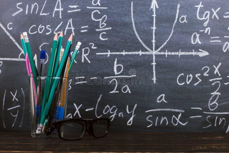 Exponeringsglas och ett exponeringsglas med blyertspennor p? svart tavlabakgrund med formler Teacher' s-dagbegrepp och baksi fotografering för bildbyråer