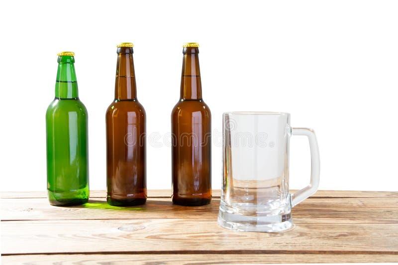 Exponeringsglas och flaska av öl med inga logoer på trätabell isolerat kopieringsutrymme, flaskåtlöje upp Ölflaskastudioskott med arkivbild