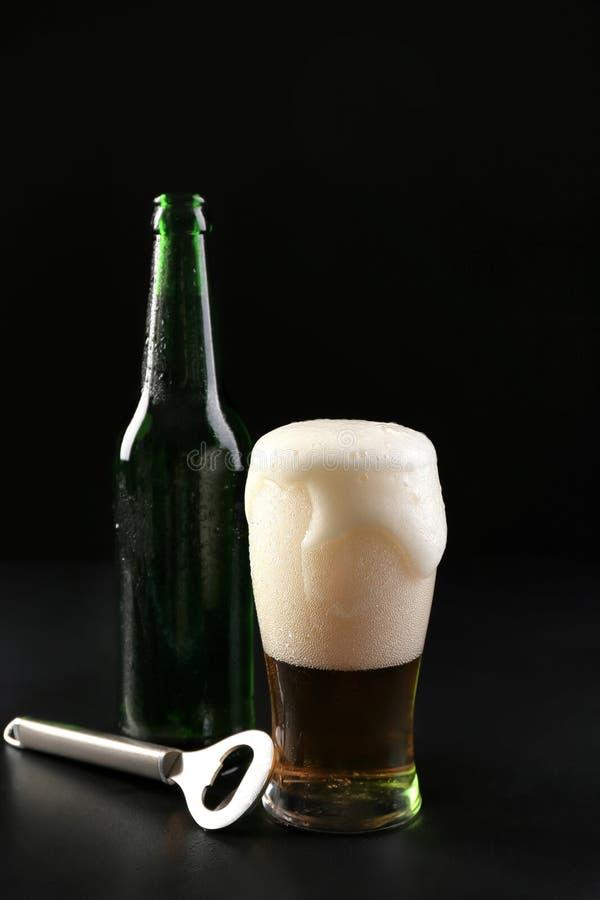 Exponeringsglas och flaska av kallt öl med öppnaren på mörk bakgrund royaltyfri foto