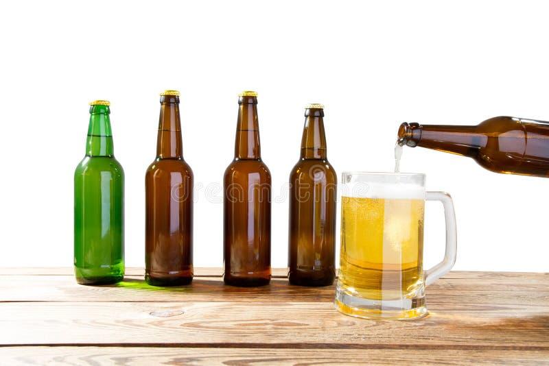 Exponeringsglas och flaska av ?l med inga logoer p? tr?tabell isolerat kopieringsutrymme, flask?tl?je upp ?lflaskastudioskott med arkivbild