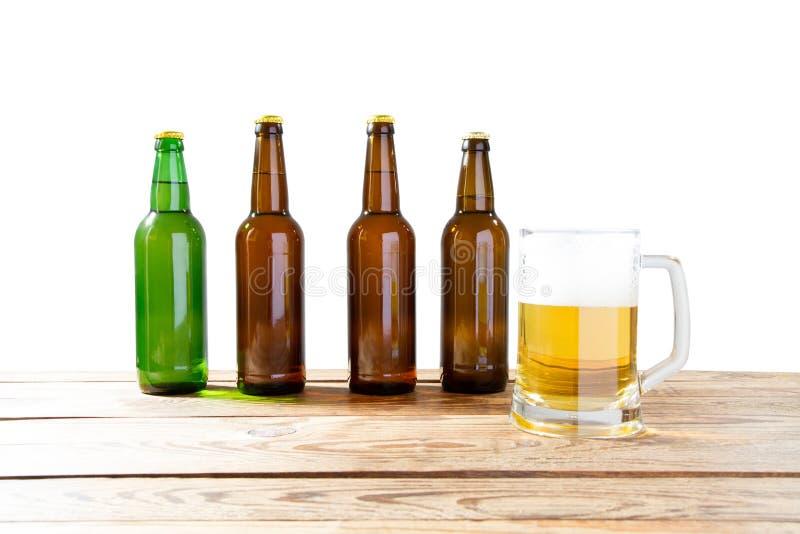 Exponeringsglas och flaska av ?l med inga logoer p? tr?tabell isolerat kopieringsutrymme, flask?tl?je upp ?lflaskastudioskott med royaltyfri fotografi