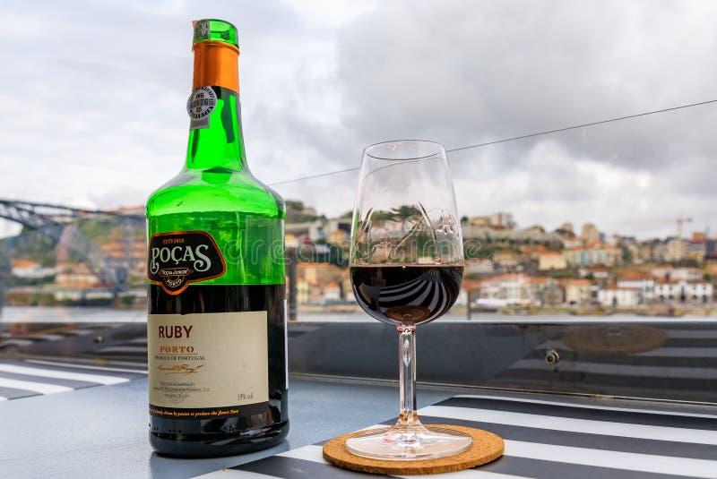 Exponeringsglas och flaska av portvin med suddig cityscape av Porto Portugal i bakgrunden royaltyfria foton