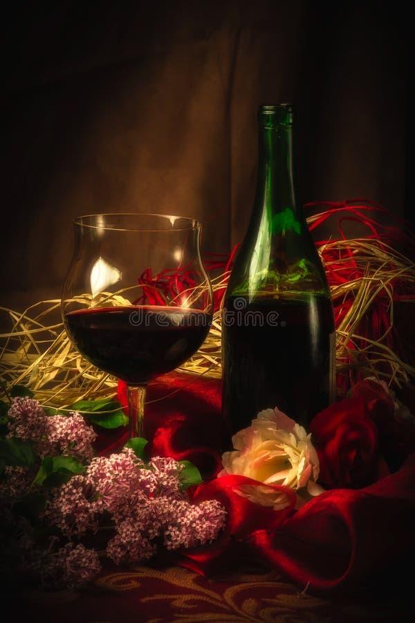 Exponeringsglas och flaska av rött vin i elegant inställning under mjukt ljus arkivbild