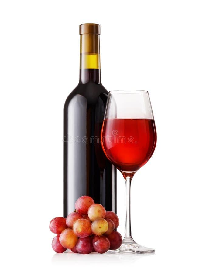 Exponeringsglas och flaska av rött vin med druvor arkivbilder