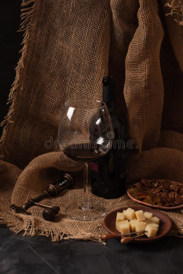 Exponeringsglas och flaska av rött vin med ost, russin och muttrar på säckväv, mörk bakgrund royaltyfria foton