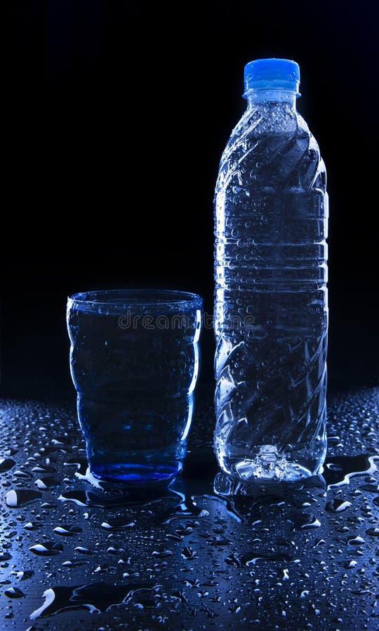 Exponeringsglas och flaska på friskhetdricksvatten på vått golv med c royaltyfria bilder