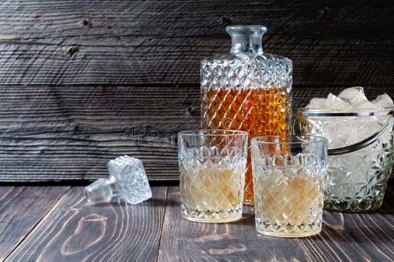 Exponeringsglas och flaskan av hård starksprit som kväv, bourbon, whisky eller konjak på träbakgrund med copyspace fotografering för bildbyråer