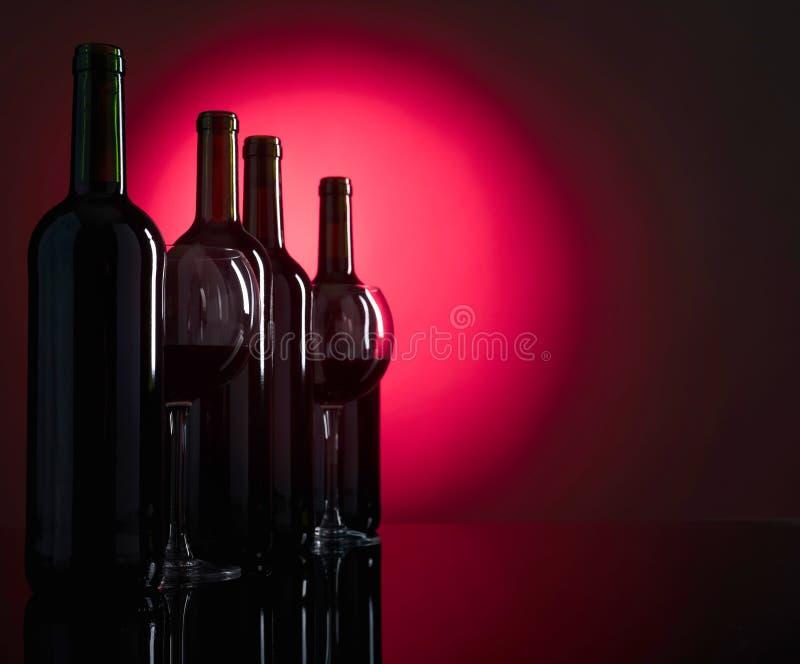 Exponeringsglas och flaskor av rött vin arkivfoto