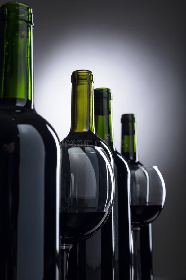 Exponeringsglas och flaskor av r?tt vin arkivfoton