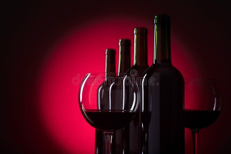 Exponeringsglas och flaskor av r?tt vin arkivfoto