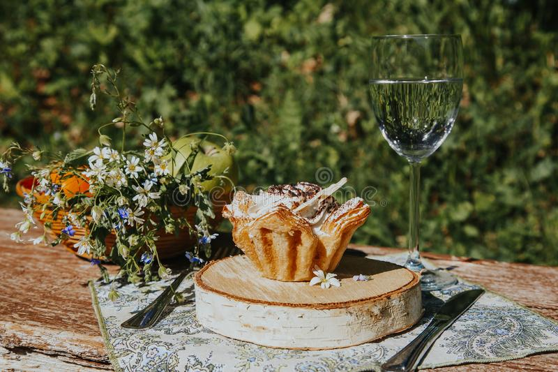 Exponeringsglas och kaka p? en solig tabell, en bukett av v?rblommor f?r lynne royaltyfri foto