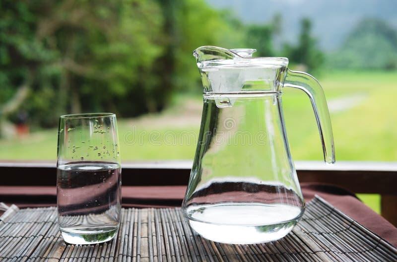 Exponeringsglas och kanna av vatten på tabellen royaltyfri bild