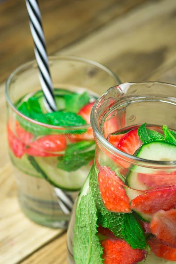 Exponeringsglas och kannan med nytt kallt ingett Detoxvatten med mogna organiska jordgubbar skivade gurkamintkaramellen Plankaträ fotografering för bildbyråer