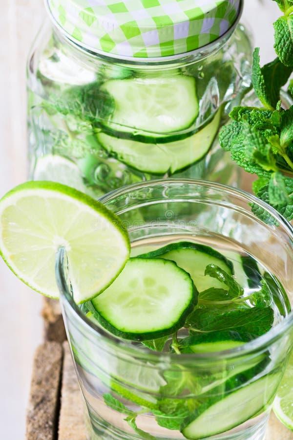 Exponeringsglas och kruset rånar med ingett detoxgurkavatten med limefrukt och den nya mintkaramellen, slut upp som rentvår arkivbilder
