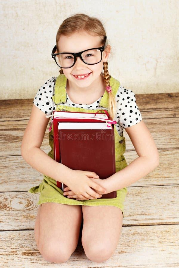 Exponeringsglas och läsning för smart flicka bärande en bok arkivbild