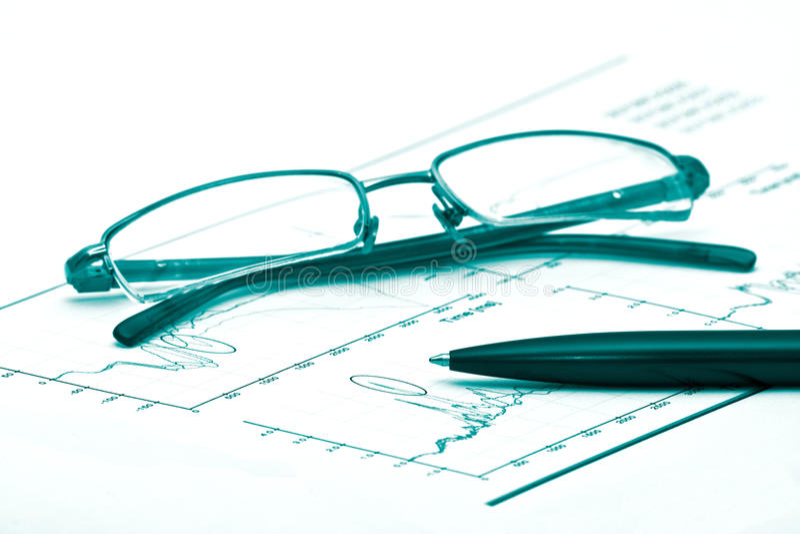 Exponeringsglas och penna på ett diagram arkivfoton