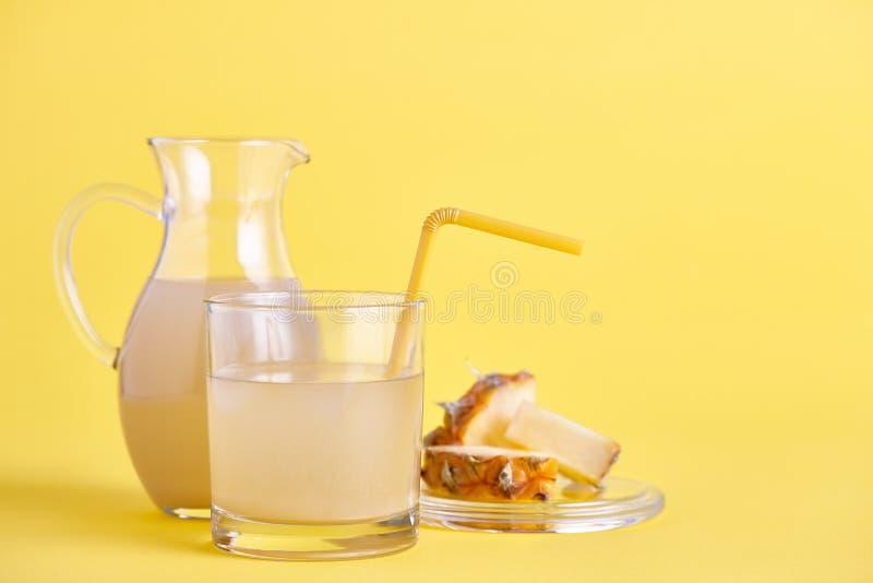 Exponeringsglas och tillbringare av ny ananasfruktsaft på guling arkivfoto