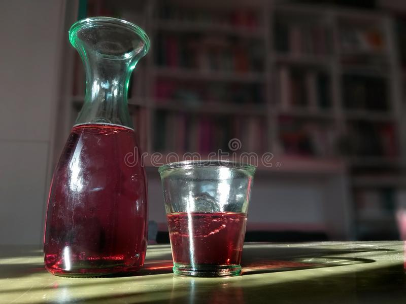 Exponeringsglas och tillbringare av rött vin på en tabell med en bokhylla på bakgrunden royaltyfri bild