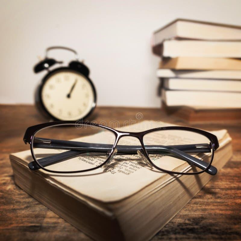 Exponeringsglas på böckerna och klockan arkivbild