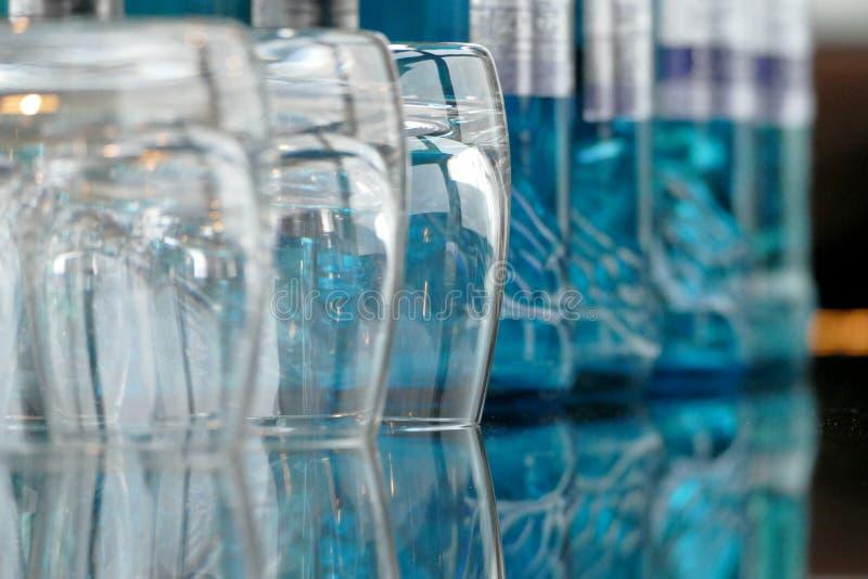 Exponeringsglas på en glass tabell med flaskor av vatten royaltyfri foto