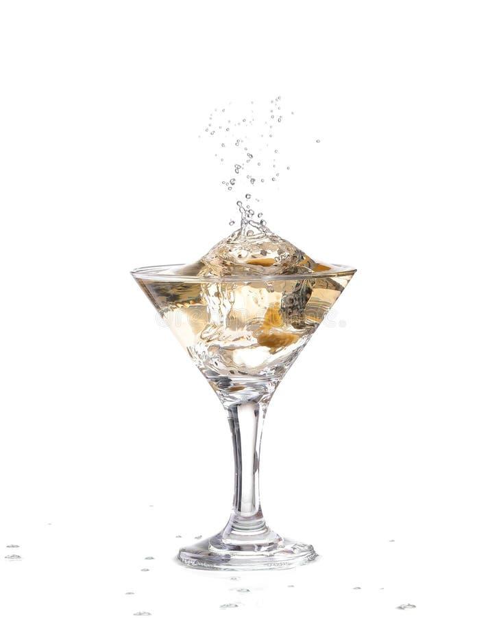 exponeringsglas på en vit bakgrund; vattenkrusningarna och plaskat, som en grön spansk oliv med kryddpepparen tappas in i glen royaltyfria foton