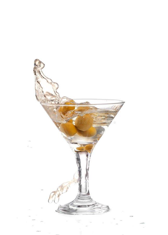 exponeringsglas på en vit bakgrund; vattenkrusningarna och plaskat, som en grön spansk oliv med kryddpepparen tappas in i glen royaltyfri bild