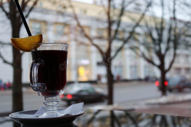 Exponeringsglas rånar med brunt, smakligt, varmt, doftande svart te med en skiva av citronen och ett sugrör på tabellen i ett kaf royaltyfri foto