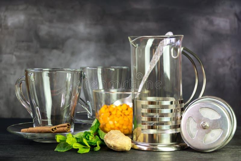 Exponeringsglas rånar och fransk press i förberedelsen av te för havsbuckthornen royaltyfri foto