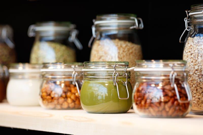 Exponeringsglas skorrar med korn, muttrar, smör, driftstopp på trähyllan på bakgrund av en mörk vägg, frukostbegreppet, kökbakgru arkivbilder