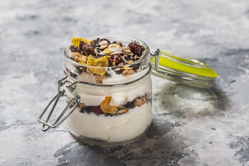 Exponeringsglas som är fullt av den vit yoghurten och mysli på ljust träbräde fotografering för bildbyråer