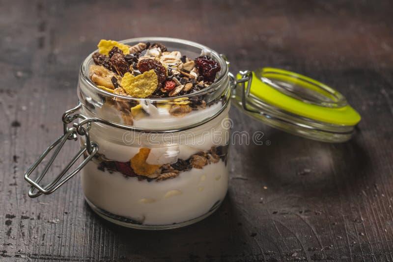 Exponeringsglas som är fullt av den vit yoghurten och mysli på mörkt träbräde arkivfoto