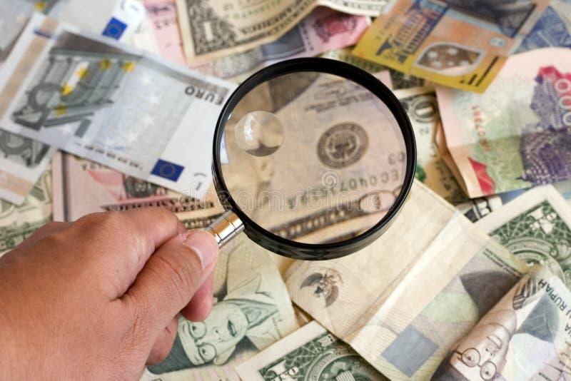 exponeringsglas som förstorar pengar arkivfoto