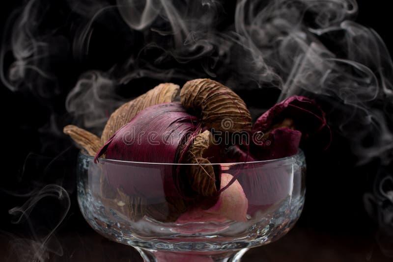 Exponeringsglas som fylls med brunt, rosa och rött potpurri med rök med svart bakgrund Rembrandt belysning inspirerade fotografering för bildbyråer