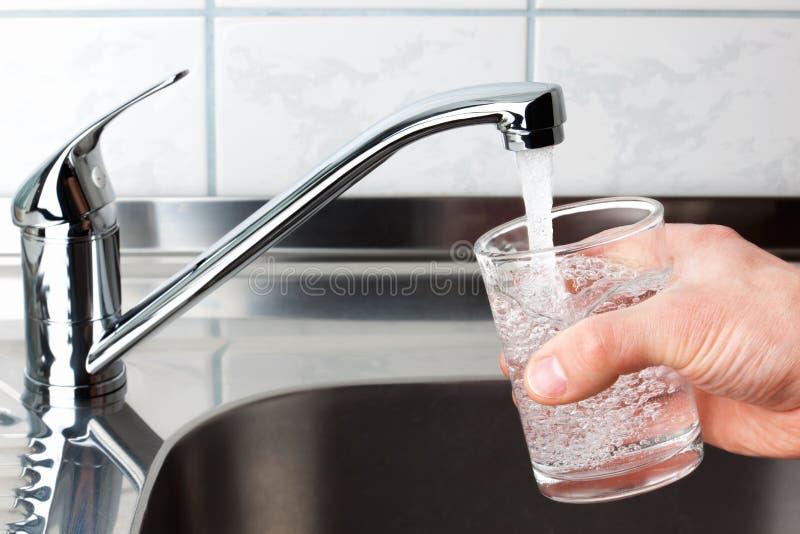 Exponeringsglas som fylls med dricksvatten från kökvattenkran. royaltyfri fotografi