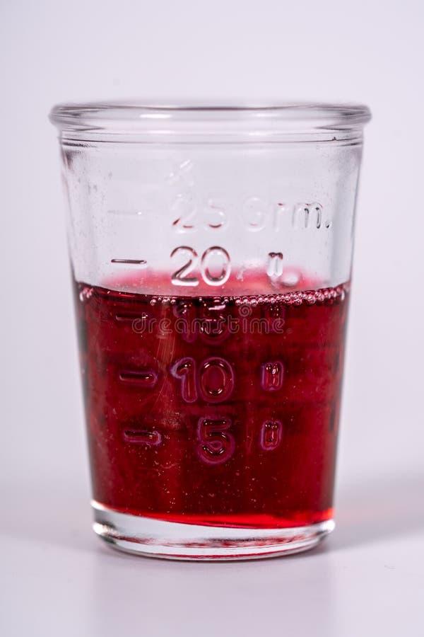 Exponeringsglas som fylls med röd medicin arkivbilder