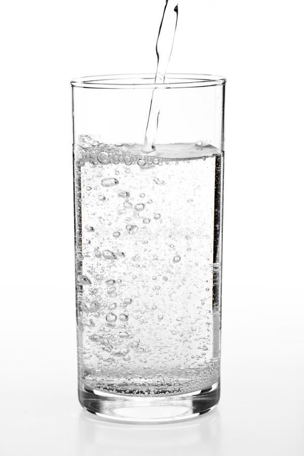 exponeringsglas som häller till vatten royaltyfria foton