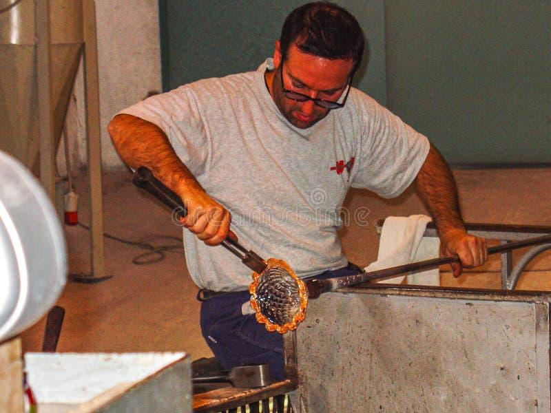Exponeringsglasblåsare som skapar en Crystal Base Murano, Italien arkivbild