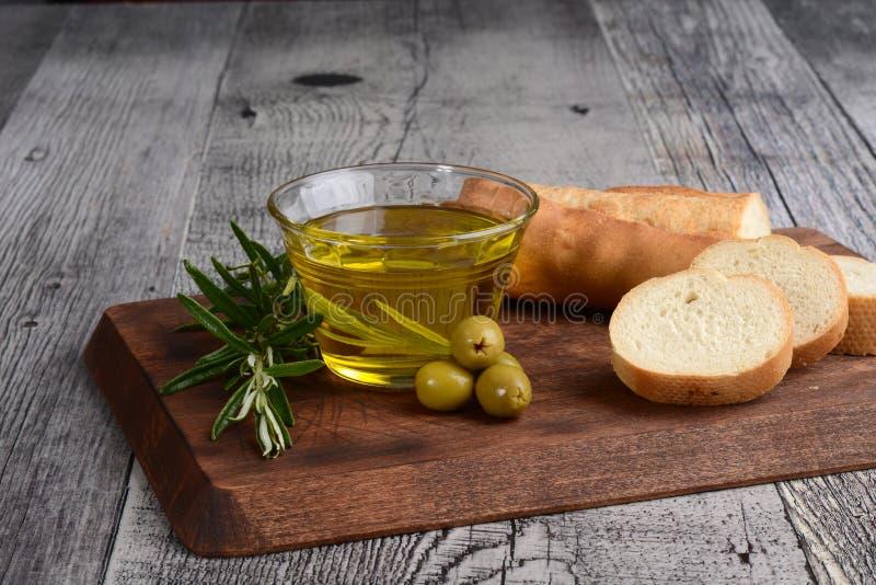 Exponeringsglasbunke av olivolja med gröna oliv och nytt bröd royaltyfria bilder