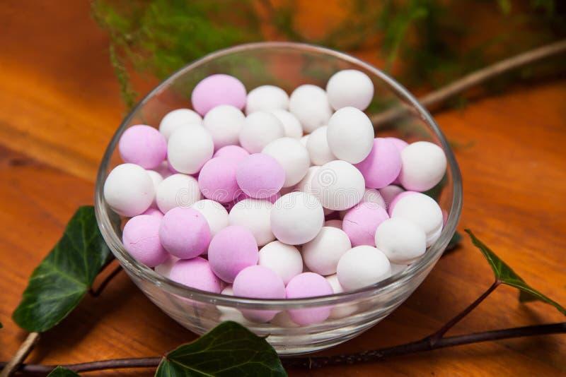 Exponeringsglasbunke med vita och rosa sockrade mandlar arkivfoto