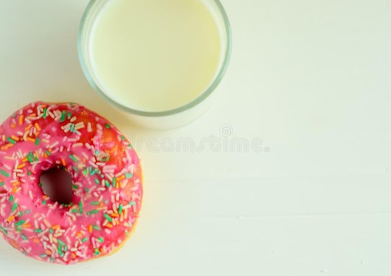 Exponeringsglaset av mjölkar och rosa färger glasade donuts på vit träbakgrund arkivfoton