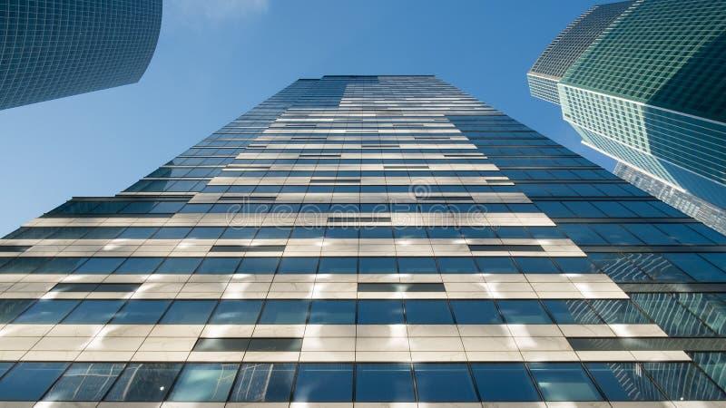 Exponeringsglasfönster av skyskrapor mot den blåa himlen arkivfoto
