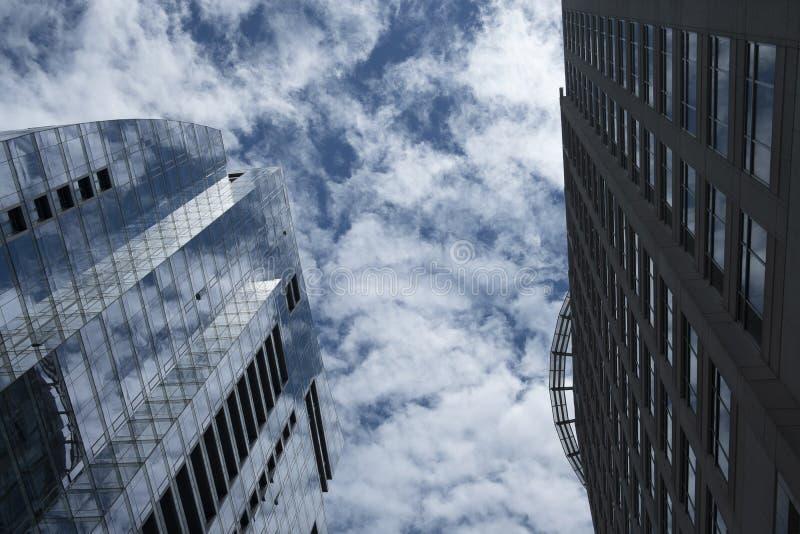 Exponeringsglasgardinväggen av kontorsbyggnaden har skuggan av blå himmel och vita moln royaltyfri foto