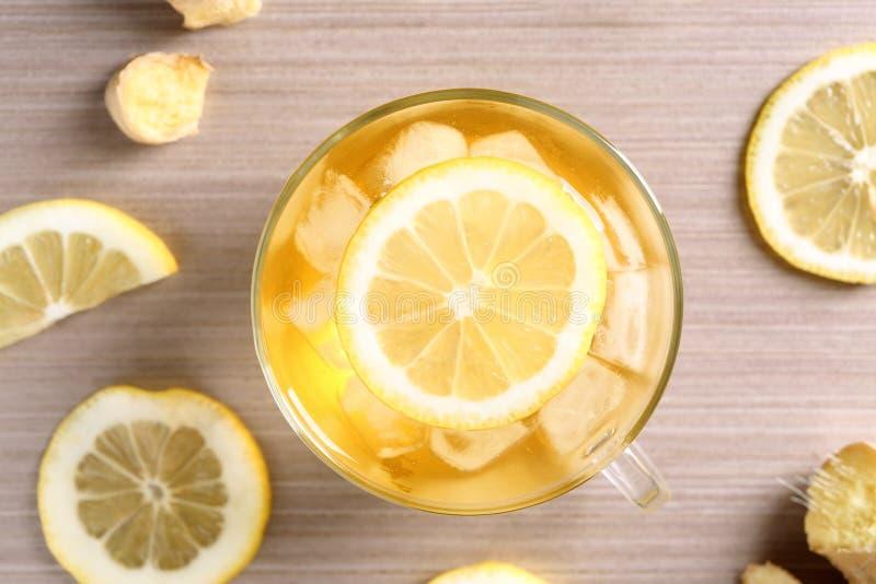 Exponeringsglaskopp av läckert te med is och citronen på tabellen arkivfoto