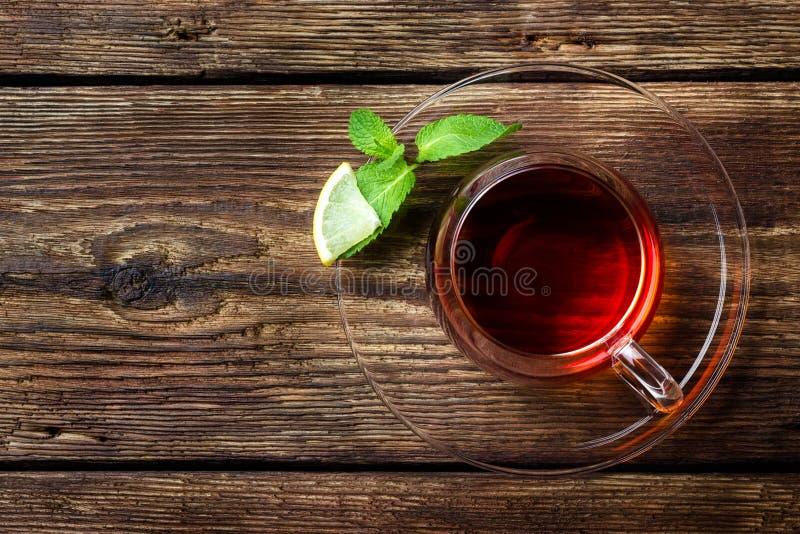 Exponeringsglaskopp med te, mintkaramellen och citronen på trälantlig bakgrund royaltyfri bild